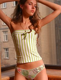 Teen fresh slim beauty in striped socks poses on put emphasize balcony.