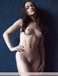 Beautiful brunet in white boots poses nude on the blue background.