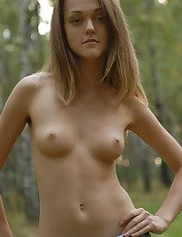 Cute youth girl takes off her blue jeans sundress and poses nude there the birchwood.
