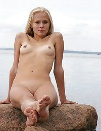 Outdoor-loving cutie, bare, open and evil among the rocky coast.