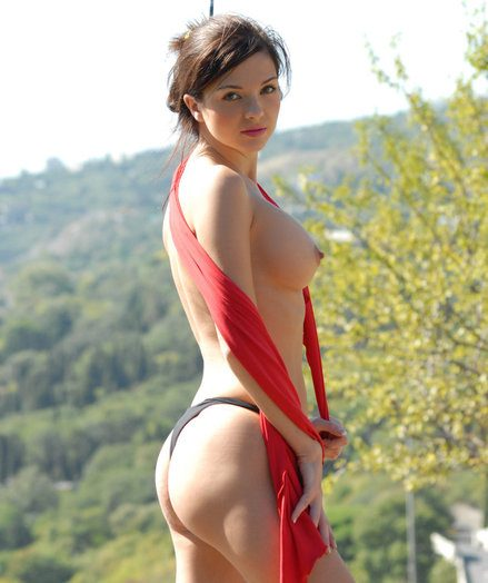 Charming super girl removes her red swimsuit and poses surpassing a wonderful lido landscape.
