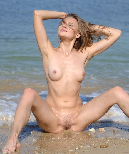 Young girl in a pink top poses nude on the XXX beach.