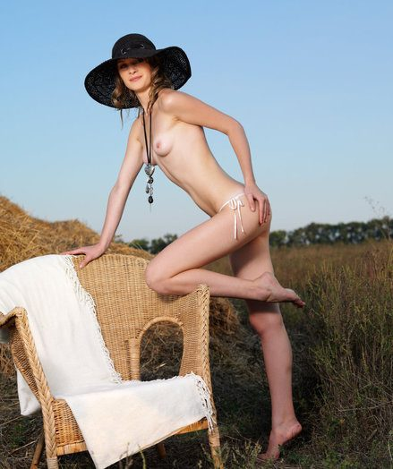 An outdoor, unversed field featuring an elegant young lassie wearing a wide-brimmed hat and her panties, posing erotically on top of a cushioned couch.