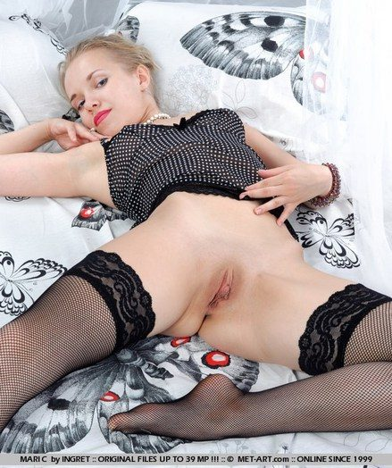 Stunning blonde showcasing her sexy hands in black fishnet stockings with lace accents.